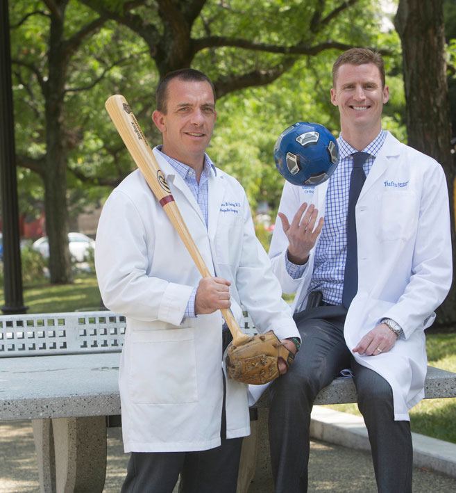 Two doctors outside holding a soccer ball and baseball bat