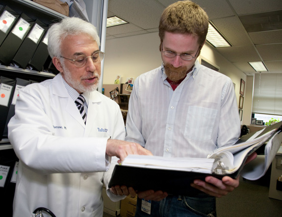 A doctor and adult reading packet of information