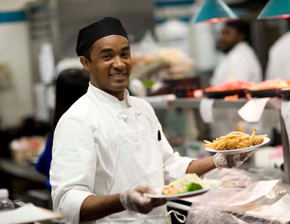 Smiling chef holding plates of food