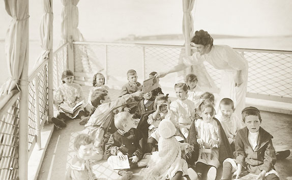 Historic photo of a nurse and a dozen children sitting on the Floating Hospital ship