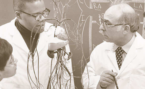 Historic photo with two physicians looking a diagram of a heart